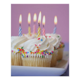 Tray of birthday cupcakes with candles poster