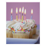 Tray of birthday cupcakes with candles posters