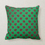 Tréboles rojos en fondo verde almohadas