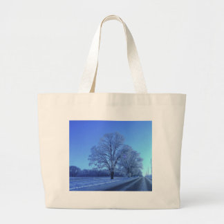Tree covered in snow on barren landscape. bags