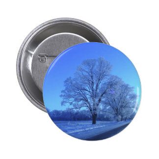 Tree covered in snow on barren landscape. button
