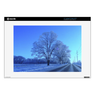 Tree covered in snow on barren landscape. laptop skins