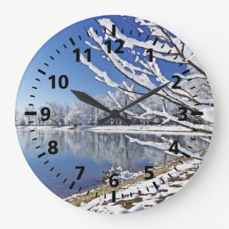 TREES COVERED IN SNOW REFLECTED IN LAKE/WALL CLOCK