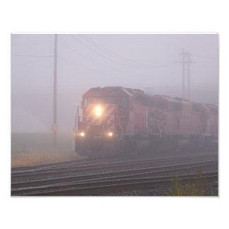 Tren de carga que corre en niebla de la mañana fotografías