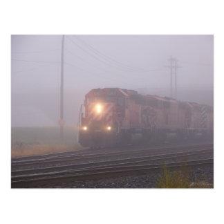 Tren de carga que corre en niebla de la mañana postales