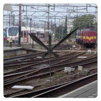Trenes de pasajeros que llegan el reloj del