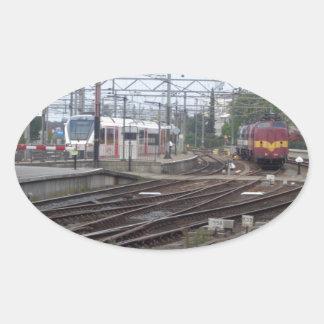 Trenes de pasajeros que llegan la estación, pegatina ovalada