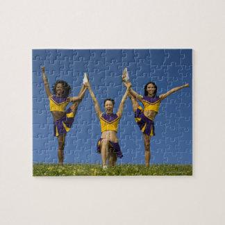 Tres animadoras femeninas que hacen la formación puzzles con fotos