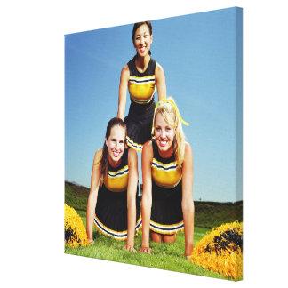 Tres animadoras que forman la pirámide humana ence impresiones en lienzo estiradas