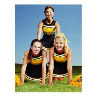 Tres animadoras que forman la pirámide humana postal