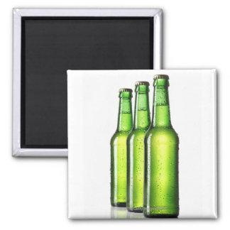 Tres botellas verdes de cerveza en el fondo blanco imán cuadrado