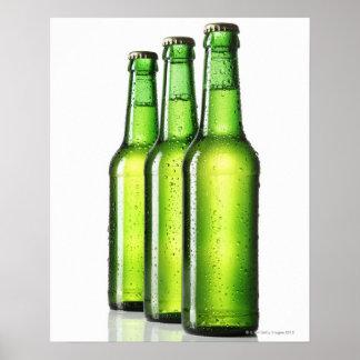 Tres botellas verdes de cerveza en el fondo blanco póster