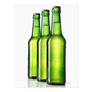 Tres botellas verdes de cerveza en el fondo blanco tarjeta postal