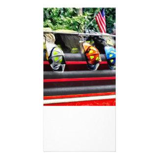 Tres cascos del fuego en el coche de bomberos tarjeta personal
