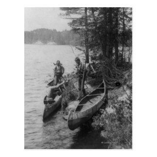 Tres cazadores con las canoas en la orilla postales