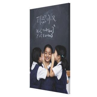 Tres chicas en el susurro de la sala de clase lona envuelta para galerías