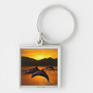 Tres delfínes en la puesta del sol llavero cuadrado plateado