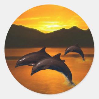 Tres delfínes en la puesta del sol etiqueta redonda
