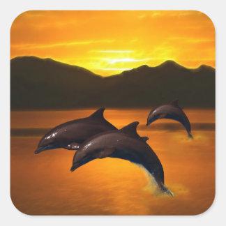 Tres delfínes en la puesta del sol pegatina cuadrada