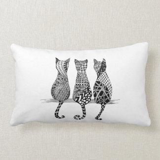 Tres gatos en una almohada de la fila en un diseño