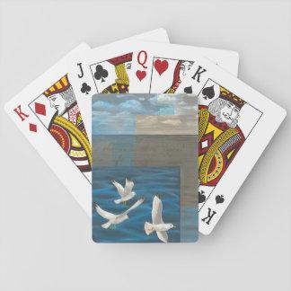 Tres gaviotas blancas que vuelan sobre el agua barajas de cartas