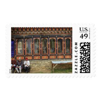 Tres hombres se sientan en un banco en el Chorten Timbres Postales
