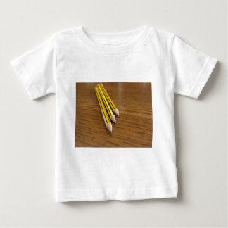 Tres lápices usados en la tabla de madera playera de bebé