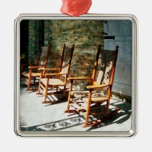 Tres mecedoras de madera en el pórtico soleado ornamento de reyes magos