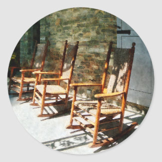 Tres mecedoras de madera en el pórtico soleado pegatinas redondas