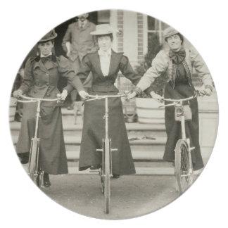 Tres mujeres en las bicicletas, 1900s tempranos (f plato de cena