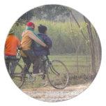 Tres niños en un ciclo en el lado del camino
