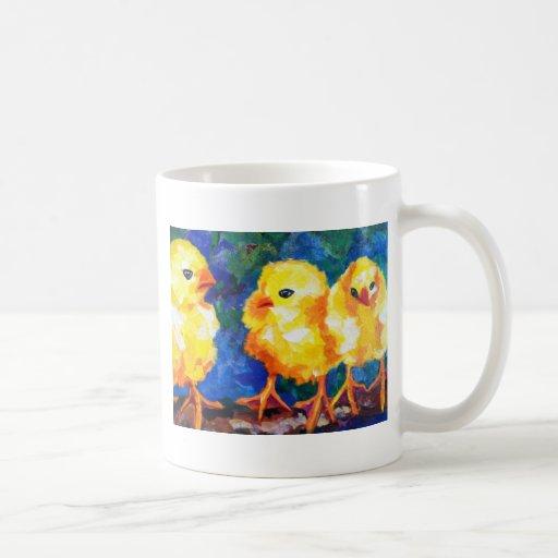 Tres polluelos profundamente en la conversación tazas de café
