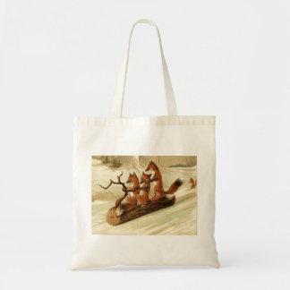 Tres zorros Sledding en una bolsa de asas del