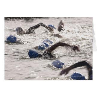 Triathletes competing in swim leg of triathlon. card