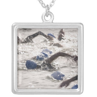 Triathletes competing in swim leg of triathlon. silver plated necklace