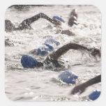 Triathletes competing in swim leg of triathlon. square sticker