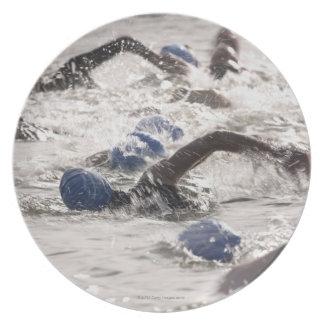 Triathletes que compite en la pierna de la nadada  platos de comidas