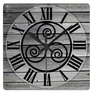 Triskelion centrado en la imagen de madera reloj cuadrado
