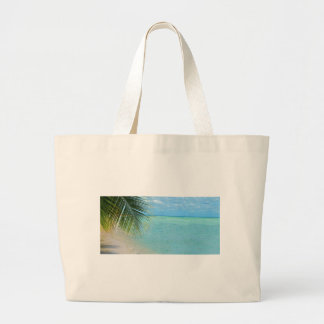 Tropical palm tree and ocean on beach tote bag
