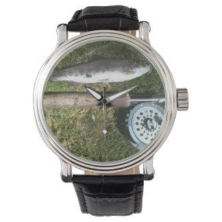 trucha arco iris, barra de pesca con mosca y relojes de mano