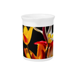 Tulip flowers against black background beverage pitcher