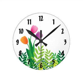 Tulipanes coloridos y vegetación verde reloj