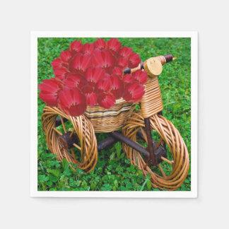 Tulipanes rojos en tenedor de mimbre de la planta servilletas desechables