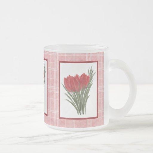 Tulipanes rojos y taza rosada de la tela escocesa