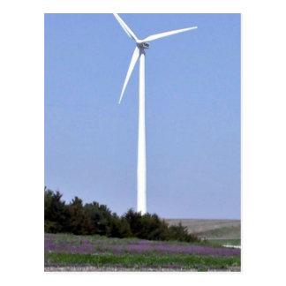 Turbina de viento detrás de un campo de flores púr tarjeta postal