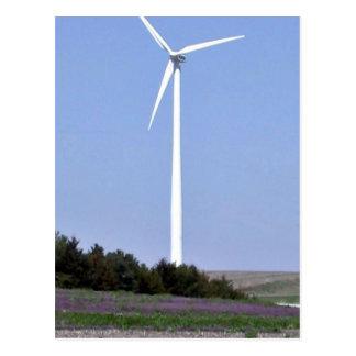 Turbina de viento detrás de un campo de flores púr tarjetas postales