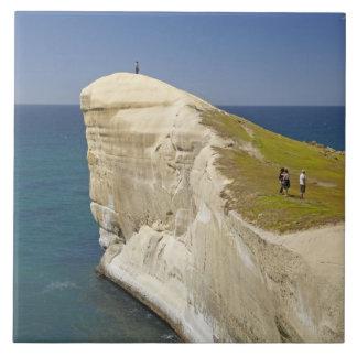 Turistas en el top del acantilado en la playa del  azulejo cuadrado grande