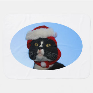 Tuxedo black and white cat with santa hat on stroller blankets