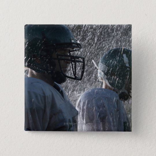 Two American football players in rain, side view Button