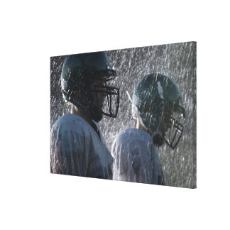 Two American football players in rain, side view Stretched Canvas Print